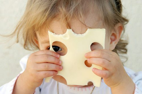 Bébé en train de se cacher le visage avec difficulté derrière une tranche de gruyère trouée