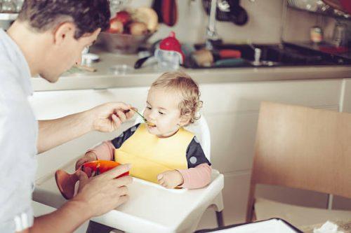 Papa en train de donner du fromage à son enfant dans la purée